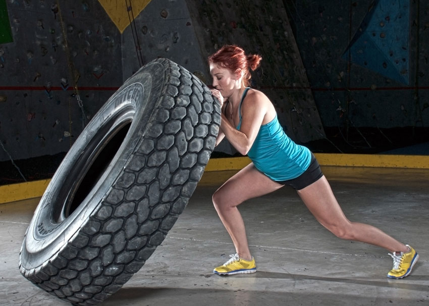 A young woman flips a tractor tire while performing CrossFit exercises in an indoor climbing gym.