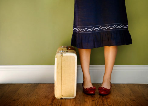 A woman stands alone with her suitcase packed