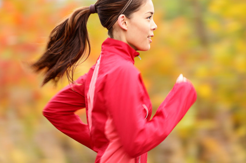 A jogger runs in the fall wearing a pink jacket
