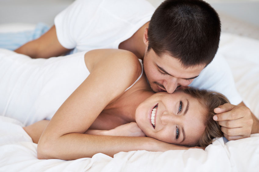A happy couple intimate in bed