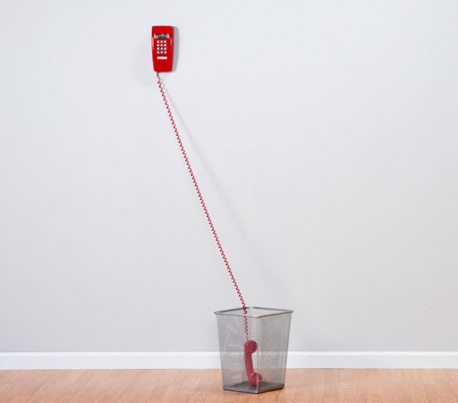 A red phone sits off the hook in a waste paper basket