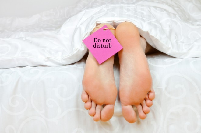 """A woman's feet in bed with a """"do not disturb"""" sign"""