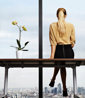 blonde-business-woman-in-office-looking-out-window-skyrise