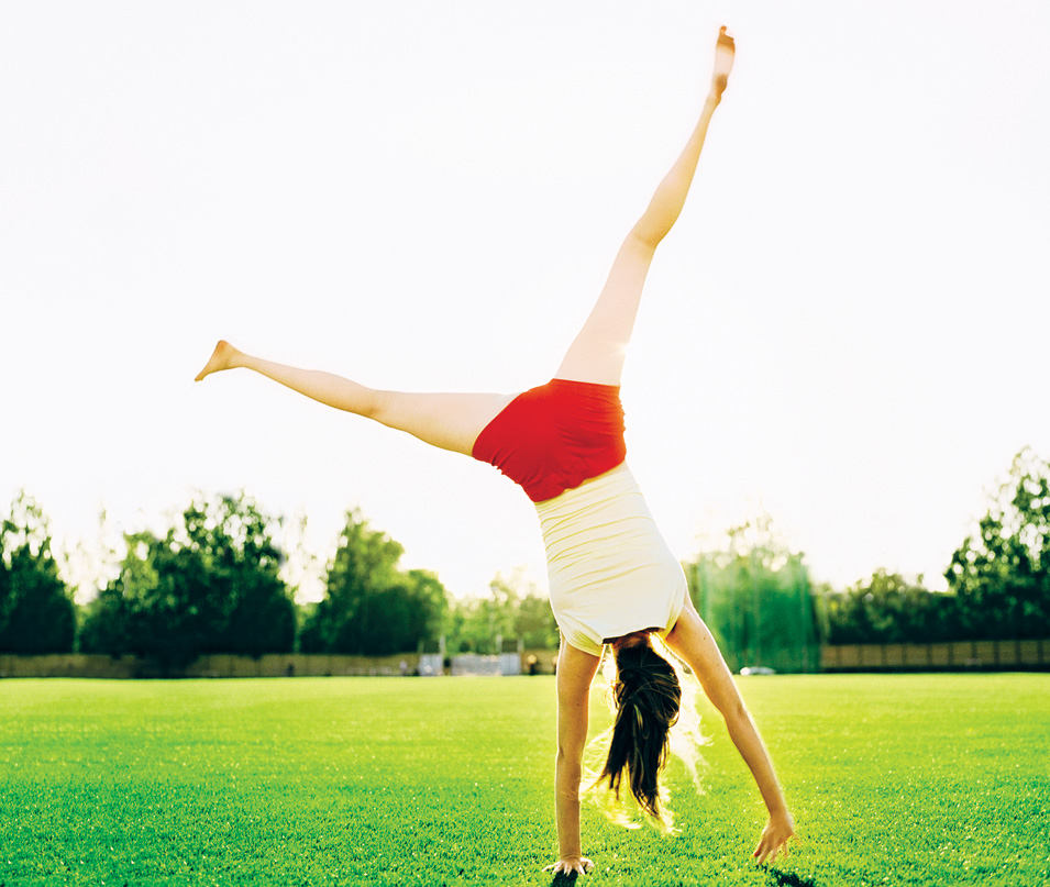 Happy Woman doing a Cartwheel in the park