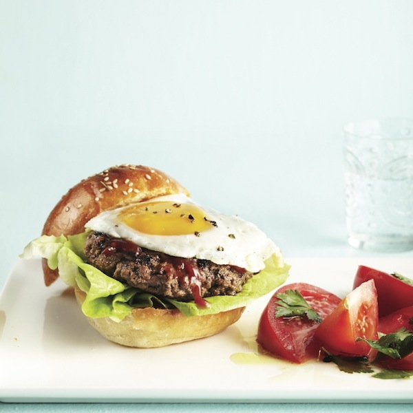 Steak and egg burger with tomato salad
