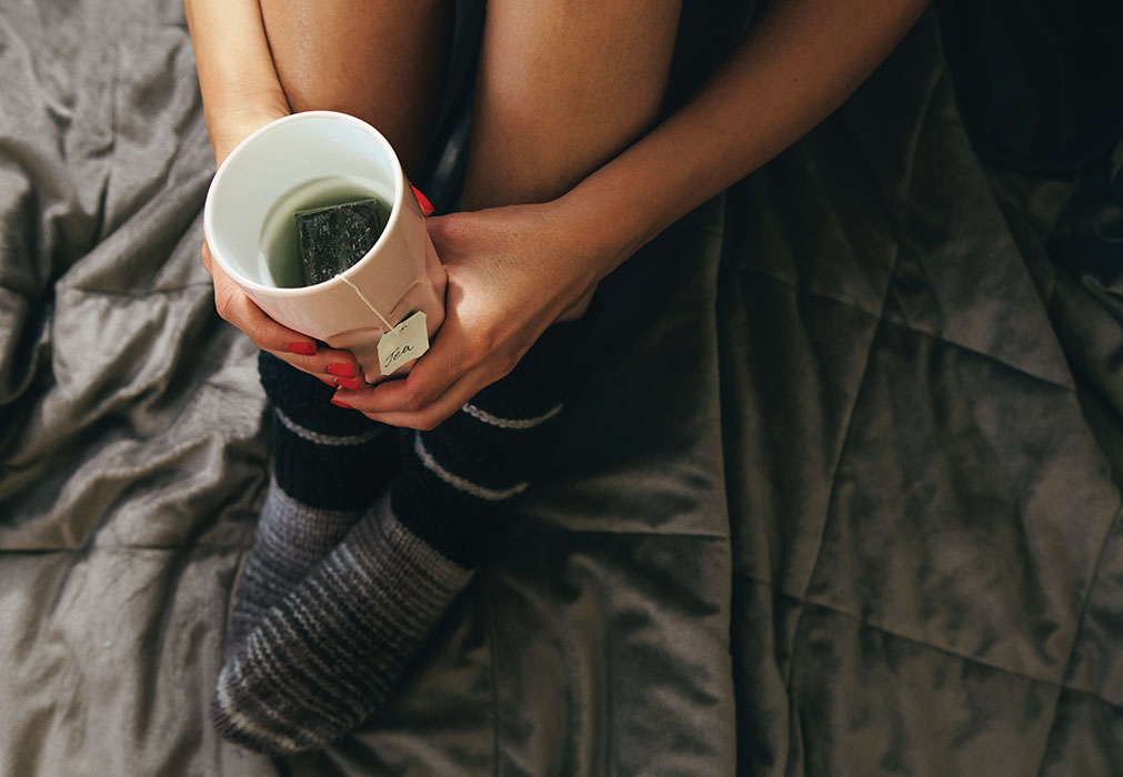 Woman holding teacup in bed