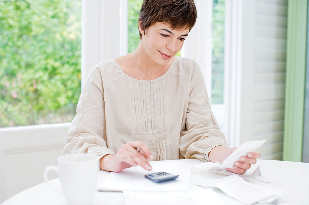 Woman calculating doing math or taxes on a calculator calculating personal finance and money