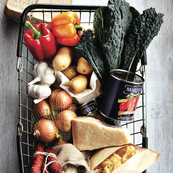 How max out the shelf life of fruits and vegetables: Image of a grocery basket filled with kale, cheese, potatoes, tomatoes, garlic and peppers