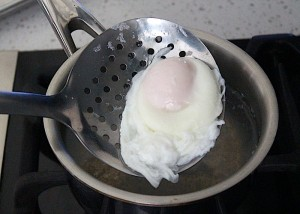 Removing poached egg from water