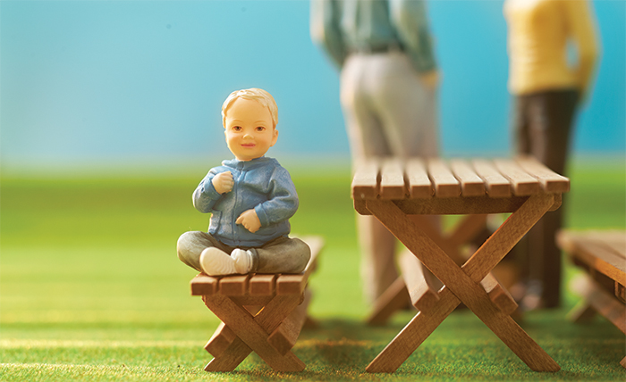Miniature baby figurine with parents, mother and father, in the background.