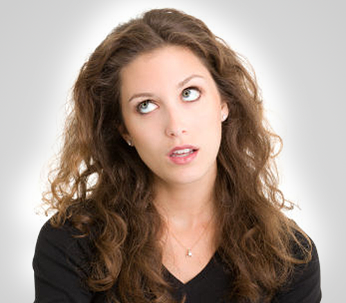 Woman with brown hair rolling her eyes, doing an eye roll