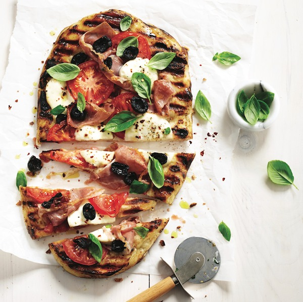 Easy dinner recipes: Grilled pizza on parchment with rolling pizza cutter