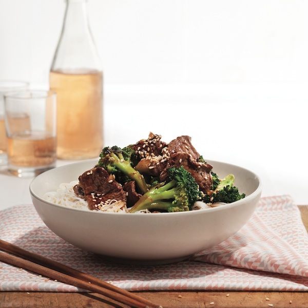 beef and broccoli on top of vermicelli in a bowl