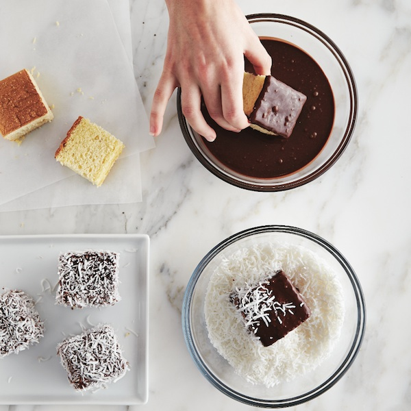 Dipping lamingtons into chocolate and coconut