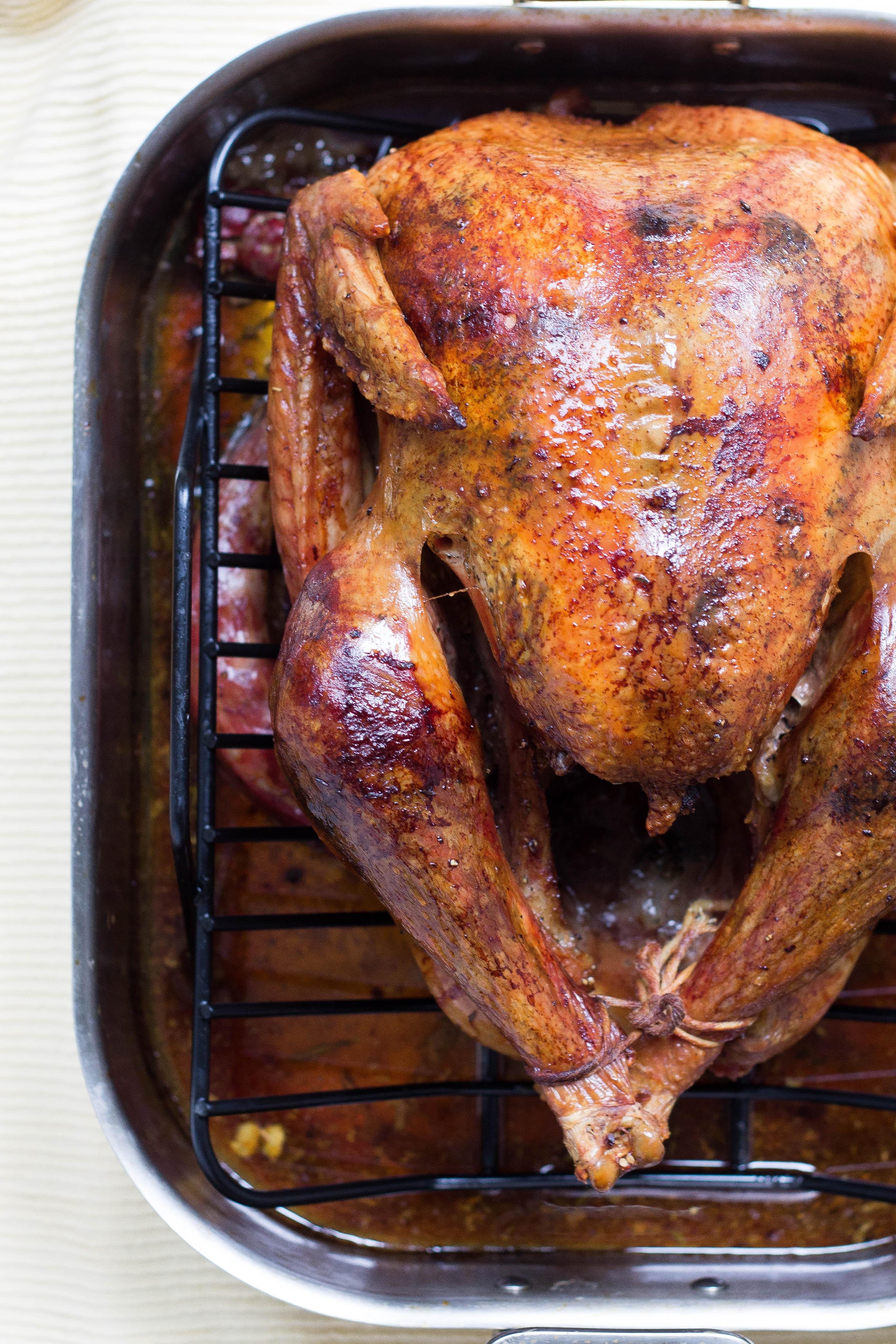 roasted turkey on roasting rack and pan