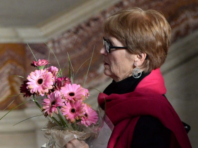Lee Carter holds a bouquet of flowers inside The Supreme Court of Canada in Ottawa on Friday morning, Feb. 6, 2015. She and her husband accompanied her 89-year-old mother Kathleen (Kay) Carter, who suffered from spinal stenosis, to Switzerland in 2010 to end her life. The Supreme Court will rule Friday morning on whether mentally competent but suffering, terminally ill patients have a right to a medically assisted death. Photo, The Canadian Press/Sean Kilpatrick.
