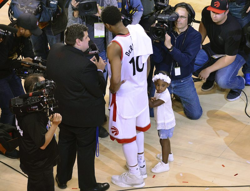 epa05309025 Toronto Raptors guard DeMar DeRozan (C) talks with reporters while holding his daughter Diar after defeating the Miami Heat 116-89 in game seven in their second-round NBA Eastern Conference basketball playoffs in Toronto, Canada, 15 May 2016. The Raptors won the series. EPA/WARREN TODA CORBIS OUT