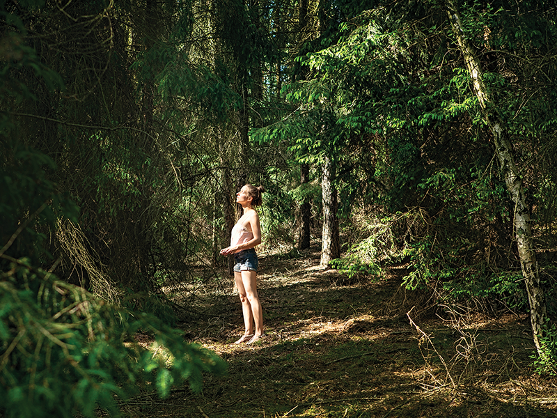 Young woman in the woods forest bathing