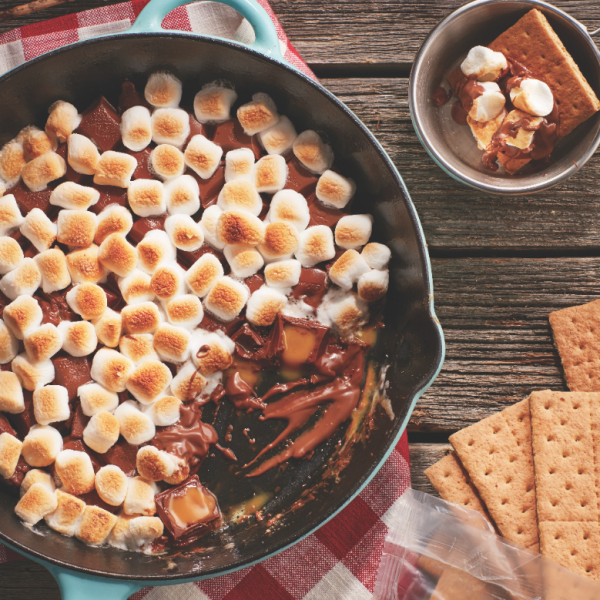 Caramel skillet s'mores recipe: one pan of s'mores on a picnic table with graham crackers on the side