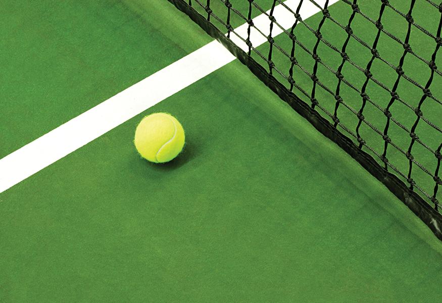 Green tennis court with tennis ball