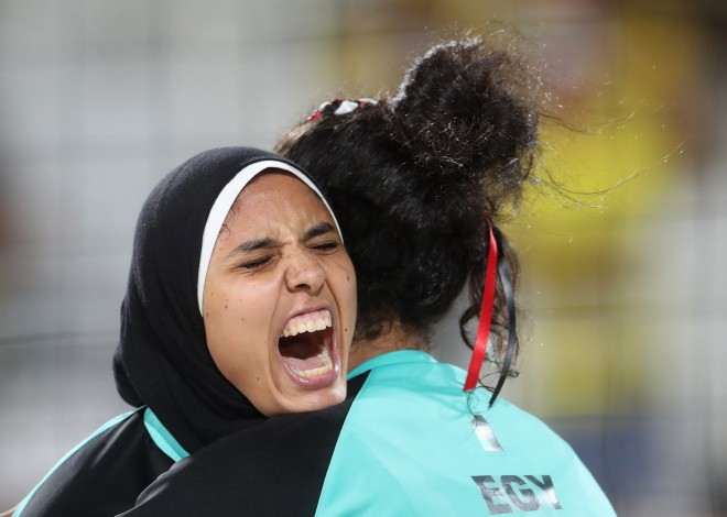 Egypt's Doaa Elghobashy, left, hugs her teammate Nada Meawad, right, during a women's beach volleyball match against Germany at the 2016 Summer Olympics in Rio de Janeiro, Brazil, Sunday, Aug. 7, 2016. (AP Photo/Petr David Josek)
