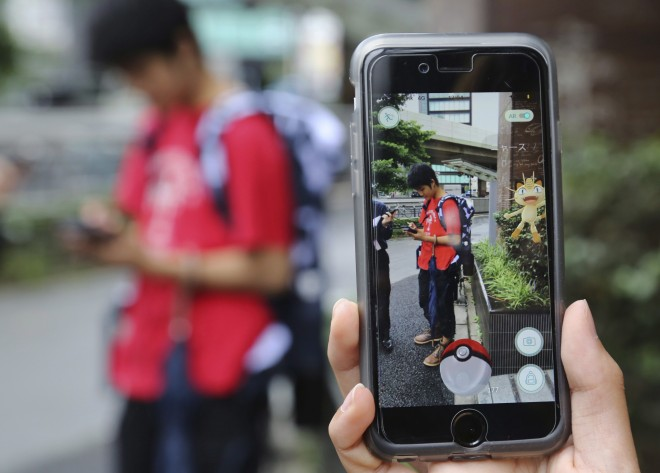 """FILE - In this July 22, 2016 file photo, Japanese students play """"Pokemon Go"""" in the street as its released in Tokyo. Japanese video game maker Nintendo Co. has sunk into a loss of 24.53 billion yen ($232 million) for the fiscal first quarter through June, 2016 despite the global success of the """"Pokemon Go"""" augmented reality game. The result Wednesday, July 27, 2016, was worse than the 673 million yen ($6.4 million) profit forecast by analysts surveyed by FactSet. (AP Photo/Koji Sasahara, File)"""