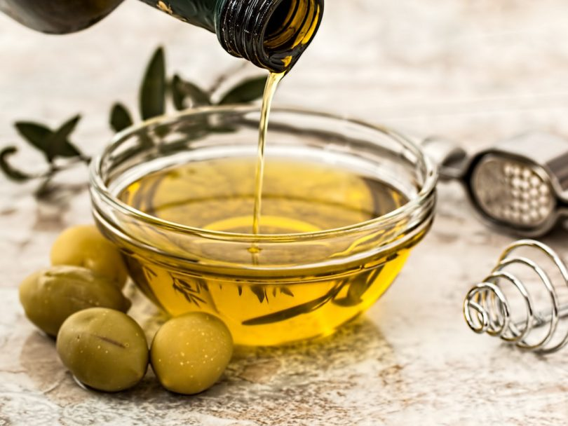olive oil health benefits-a bowl of olive oil with green olives nearby