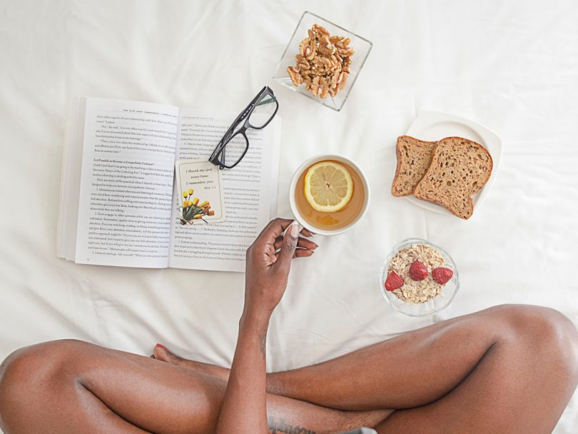 overhead flat shot of a woman sitting cross-legged in bed eating toast granola and tea