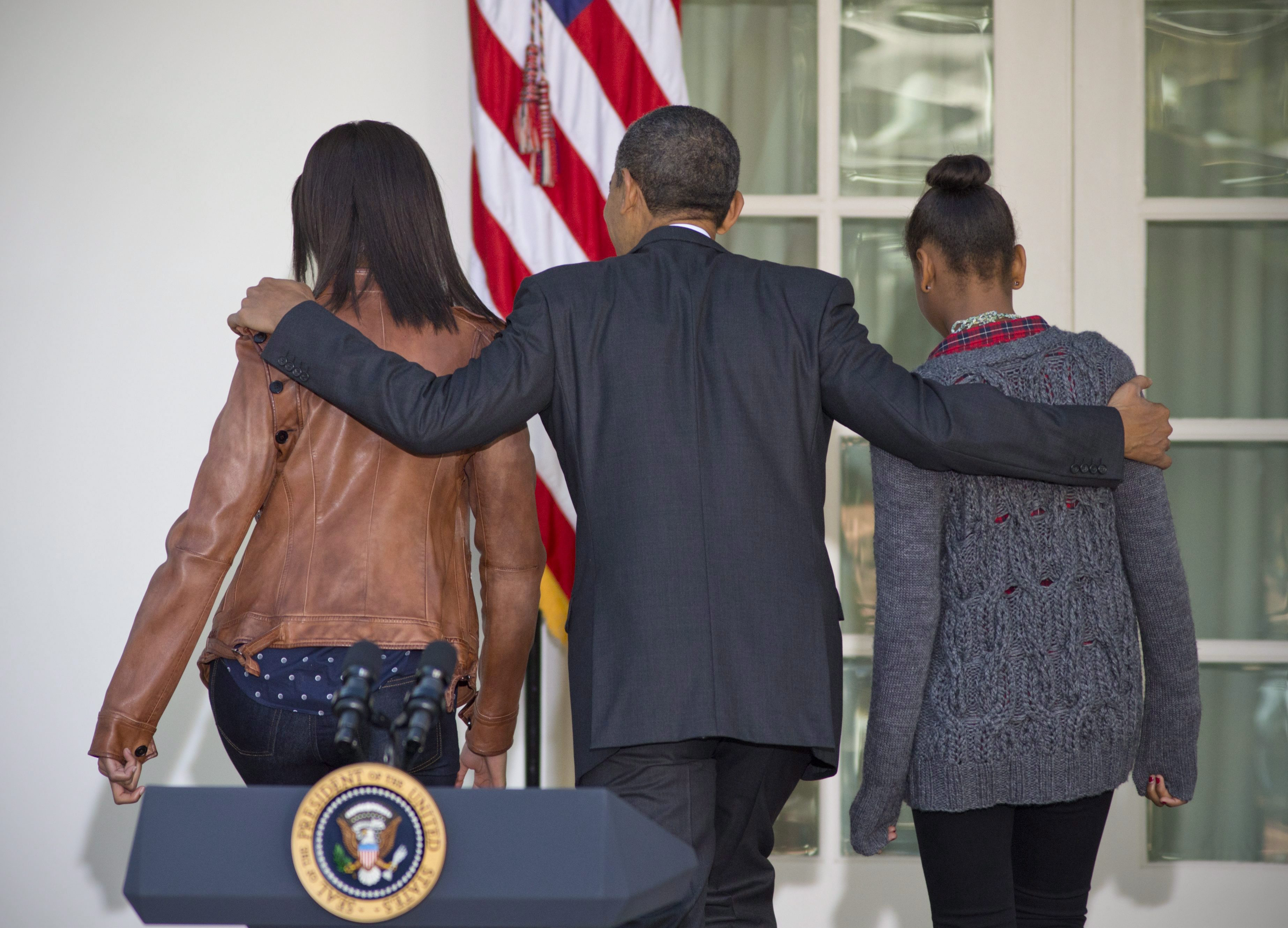 """FILE - In this Nov. 21, 2012 file photo, President Barack Obama walks with daughters Sasha, right, and Malia, left, to the Oval Office of the White House in Washington, Wednesday, Nov. 21, 2012, after a ceremony giving a """"presidential pardon,"""" to a turkey in the Rose Garden. President Barack Obama's daughter Malia was just 10 and longing for a promised puppy when her family moved into the White House. She's marked some of life's milestones in the past seven years, and another one comes Friday: graduation from high school.(AP Photo/J. Scott Applewhite, File)"""