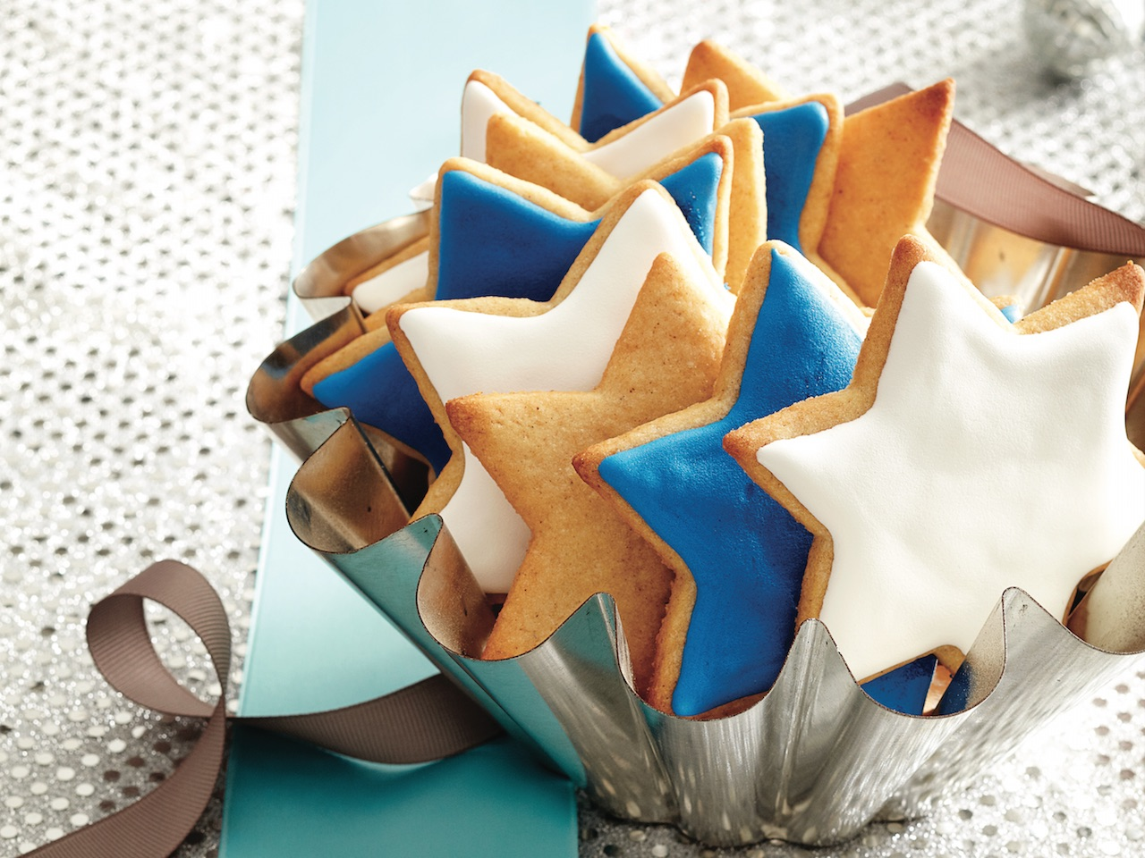 royal icing decorated start-shaped sugar cookies in a small brioche tin