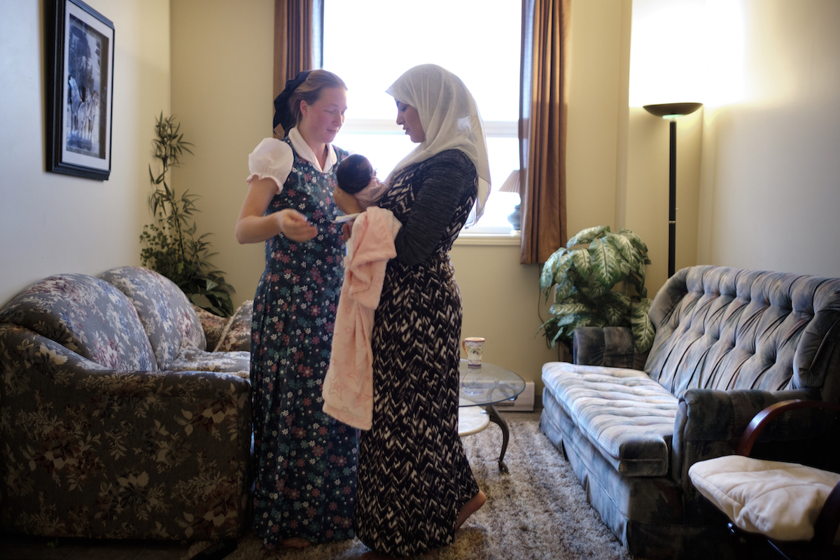 """Elaine Hofer (left) helps Najwa Hussein take care of her newborn daughter, Janna. The child, born in November 2016 in Canada, has helped strengthened the bonds between the Syrian family and the community sponsoring them. """"I would have never imagined that I'd go to the hospital and a Muslim woman would have a baby and she would feel so much like my sister,"""" says Elaine. Photo, Annie Sakkab/UNHCR."""
