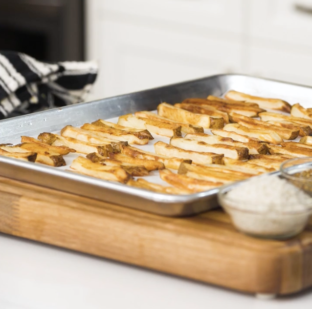 baked french fries on an aluminum baking sheet.