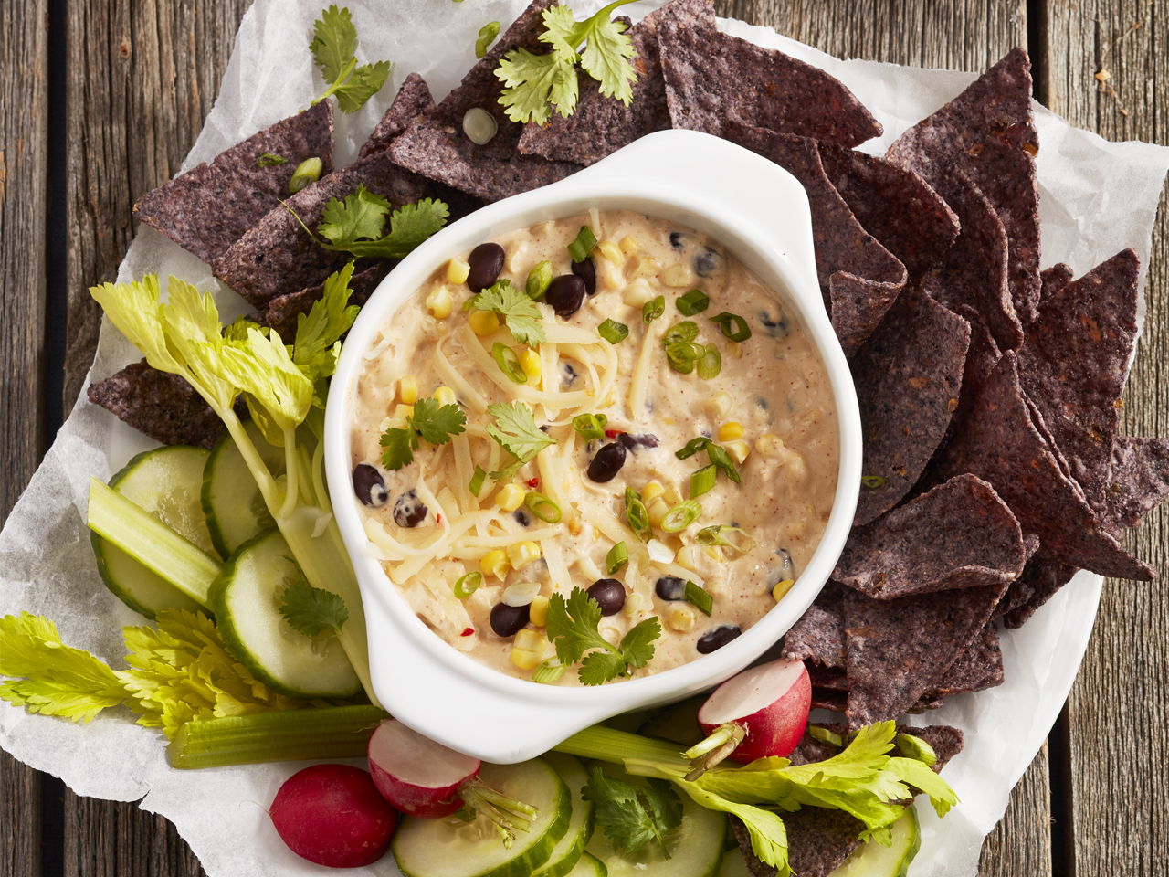southwest corn and bean cream cheese dip with vegetables and tortilla chips
