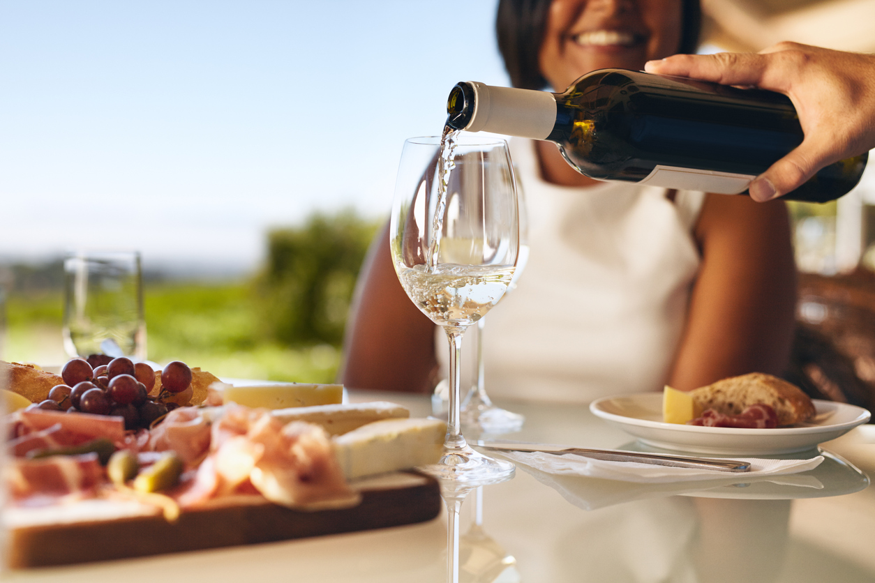 How alcohol affects women – Hands of a man pouring white wine in two glasses from bottle with a woman smiling in background at winery. Focus on glasses and wine bottle.