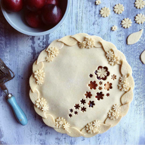 decorative pie crusts: plum pie with leaves and flowers around edge of pie with flower cut outs in middle