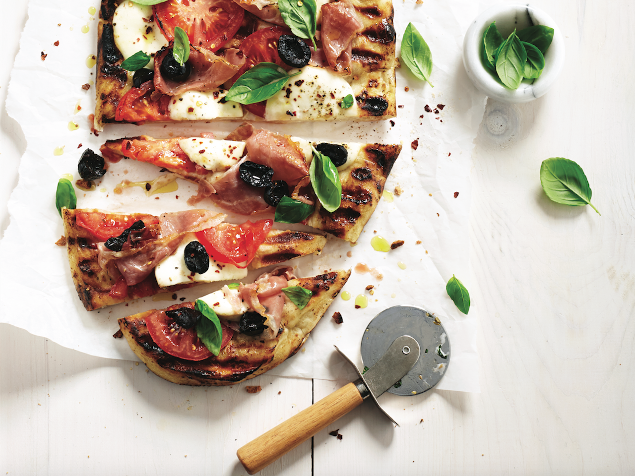Grilled pizza recipe: Partly sliced grilled pizza on a wooden cutting board, topped with cheese, basil and prosciutto.