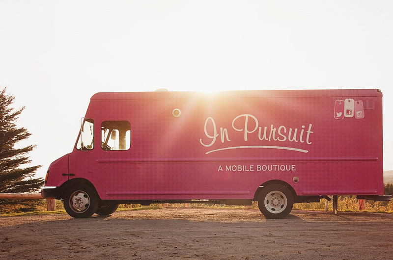 A pink truck sits on a sandy road as the sunset. It says 'In Pursuit - A Mobile Boutique' on the side.