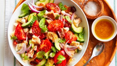 Summer dinner recipes like this Tuna panzanella salad are irresistible. Served in large white bowl on a circular wooden platter