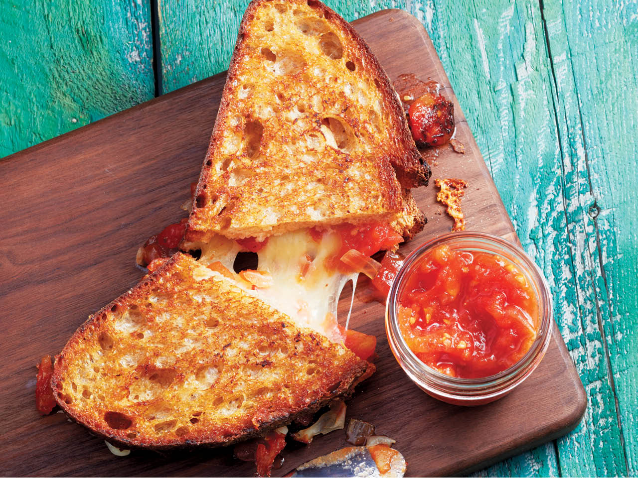 Melted cheese inside a grilled cheese with tomato jam
