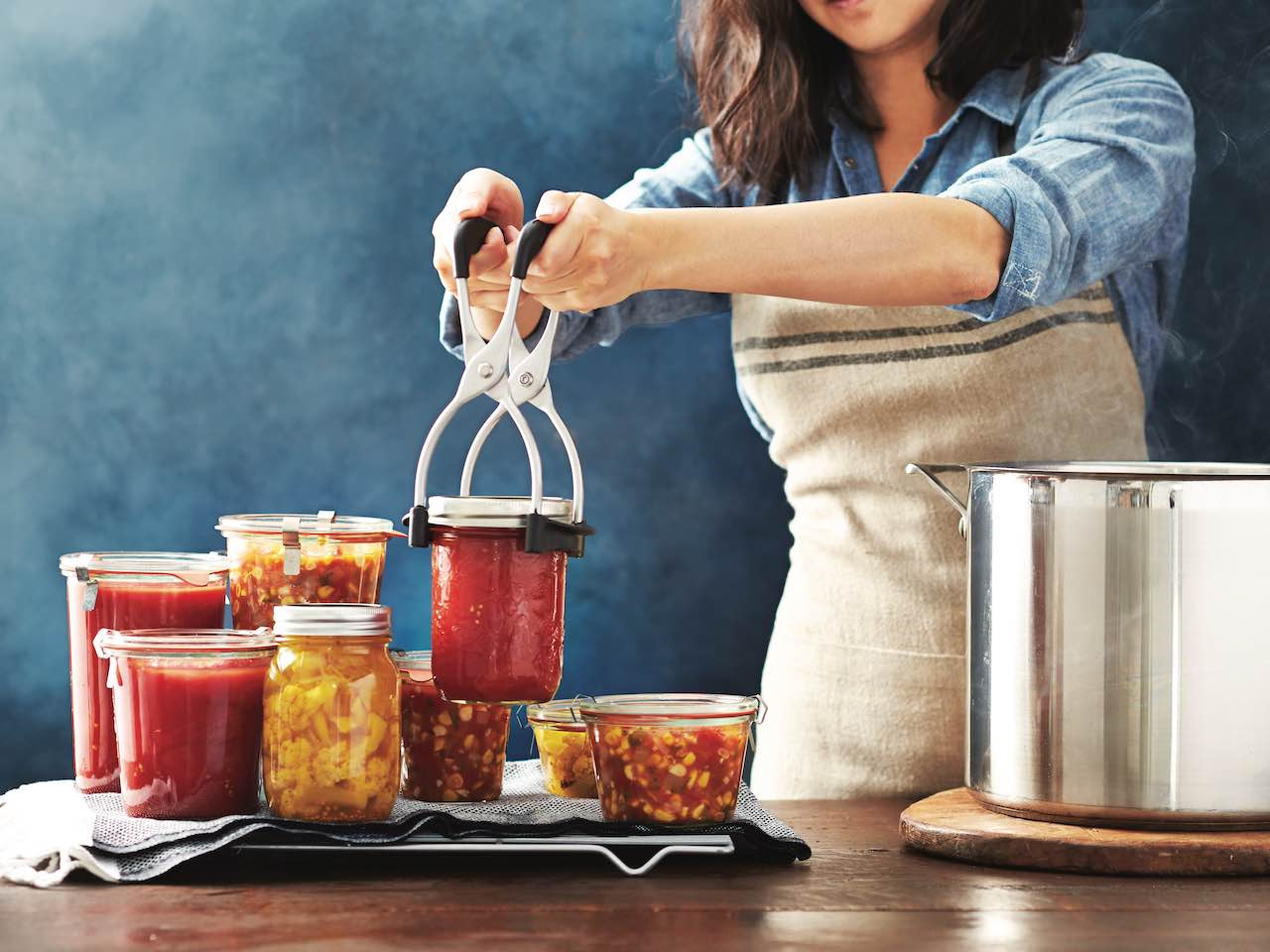 How to make preserved tomatoes: woman lifting can of preserved tomatoes