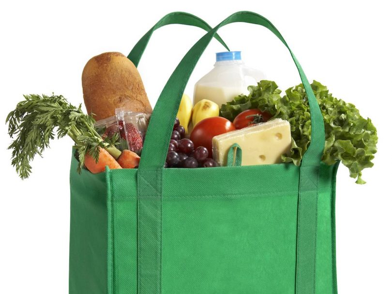 Green bag filled with groceries.