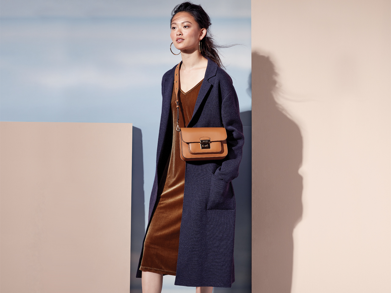 A model wears a velvet dress under an oversized cardigan.