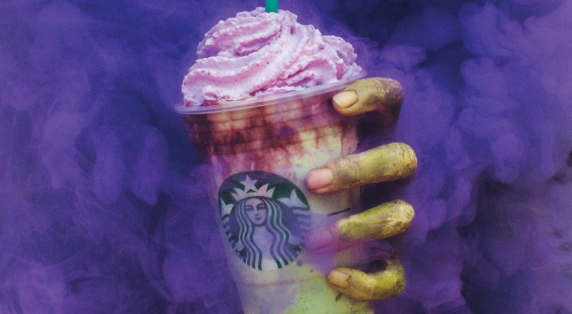 Green hand grabbing a purple and green zombie frappuccino in a Starbucks cup