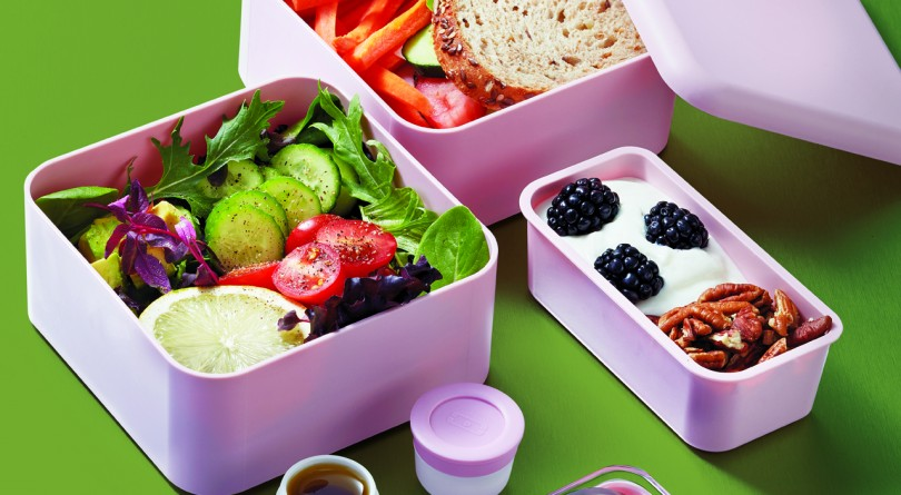 Three pink containers and fork and knife on green background