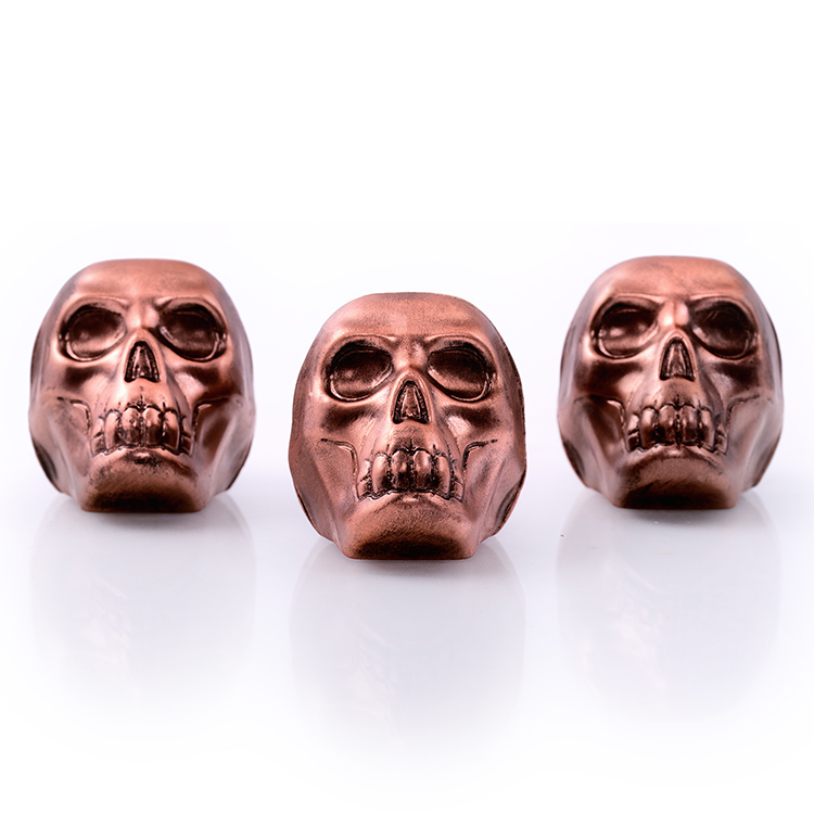 Three skulls wrapped in copper foil