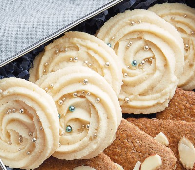 whipped shortbread cookies in rosettes with sprinkles stacked in a tin