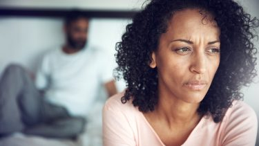 A woman looks upset with her husband, who is in the background, for a piece on whether an open marriage is ever a good idea