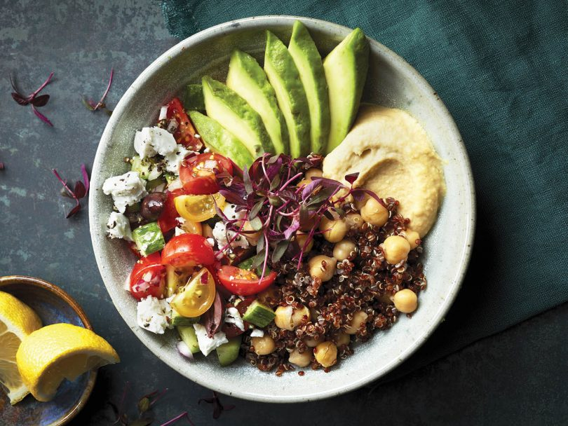 how to cook quinoa: mediterranean quinoa bowl with hummus, avocado and fresh tomatoes in a white bowl