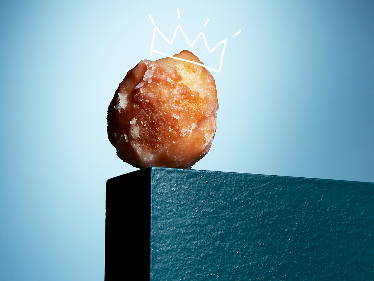 sour cream glazed Timbit on a light blue background