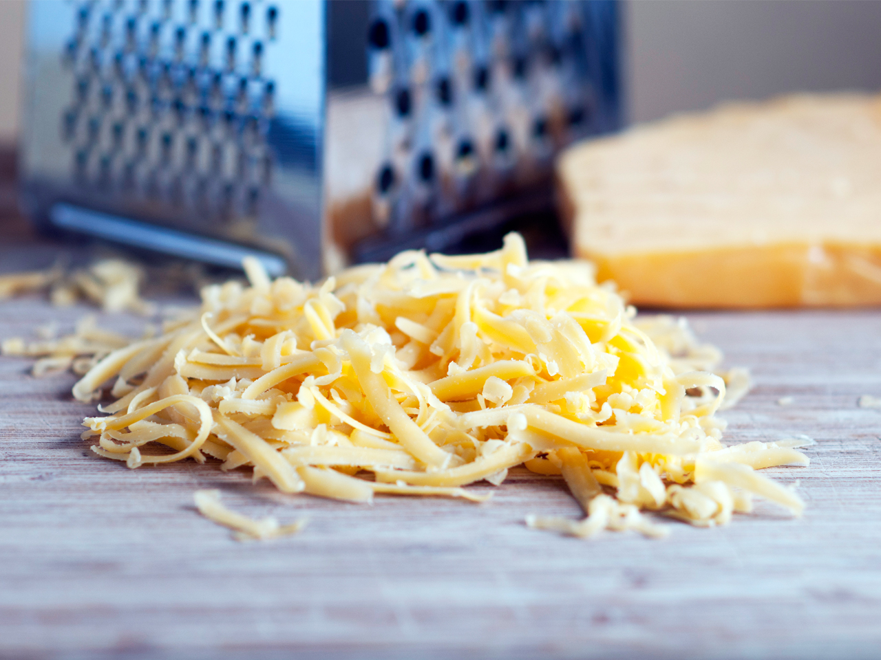 Pile of shredded cheese in front of box grater